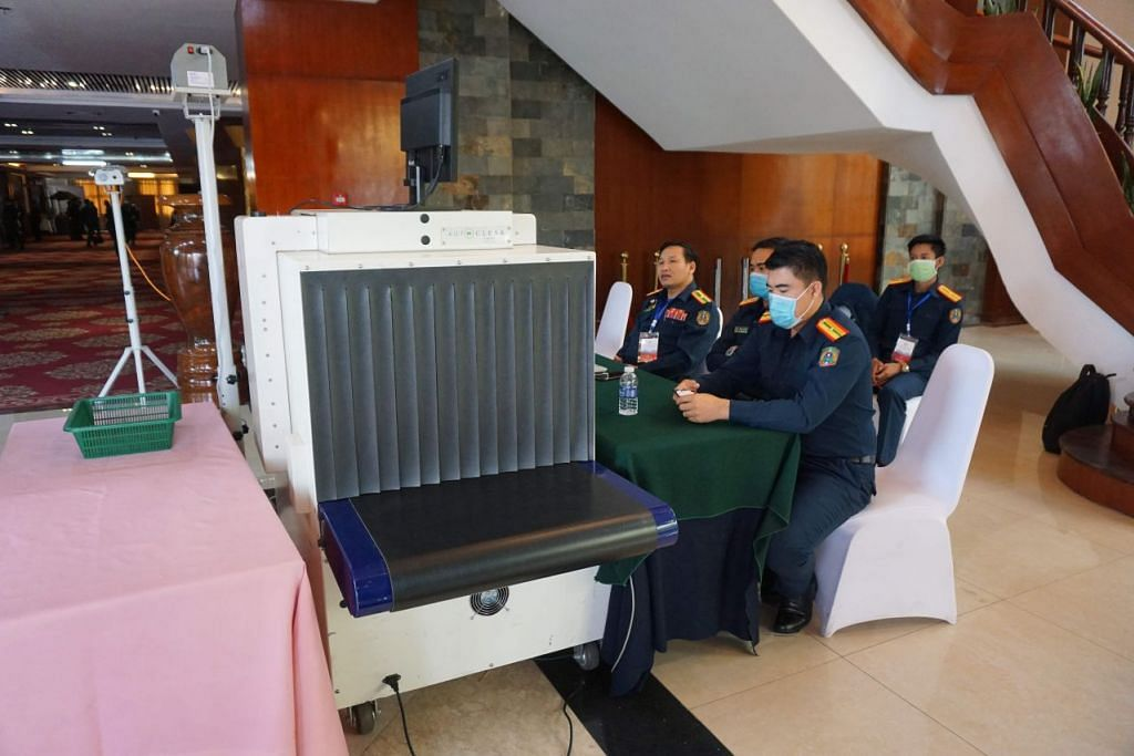 DUA KES PERTAMA: Beberapa pegawai keselamatan dilihat memakai pelitup di stesen pemeriksaan satu bangunan yang digunakan untuk acara sidang puncak koronavirus yang dihadiri Menteri Asean dan China di Vientiane Laos pada 25 Februari 2020. - FOTO: AFP