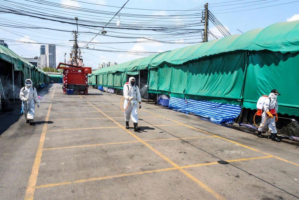 DEKRI DARURAT: Beberapa pekerja kesihatan dengan alat pelindung sedang menjalankan kerja pebasmian kuman di pasar Chatuchak, Bangkok pada 23 Mac 2020. Foto:AFP