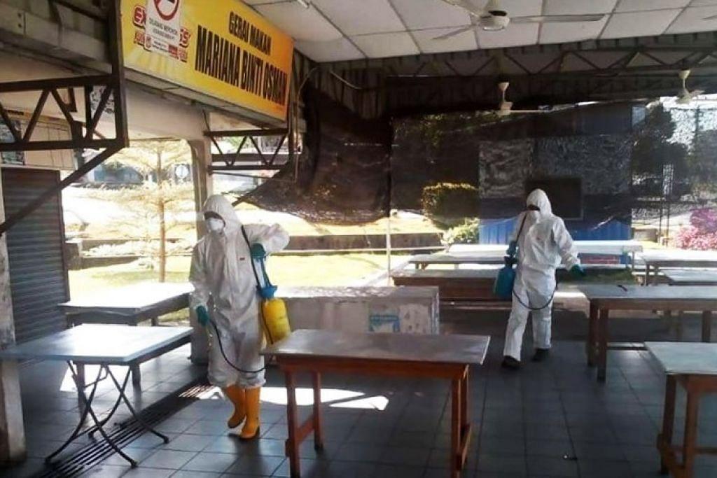 Pekerja membersihkan kedai di Simpang Renggam.