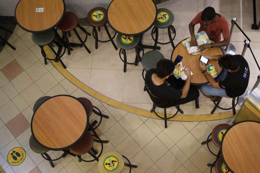 Pelekat menunjukkan perlunya duduk jarak jauh kelihatan di sebuah restoran di pusat beli-belah ini.