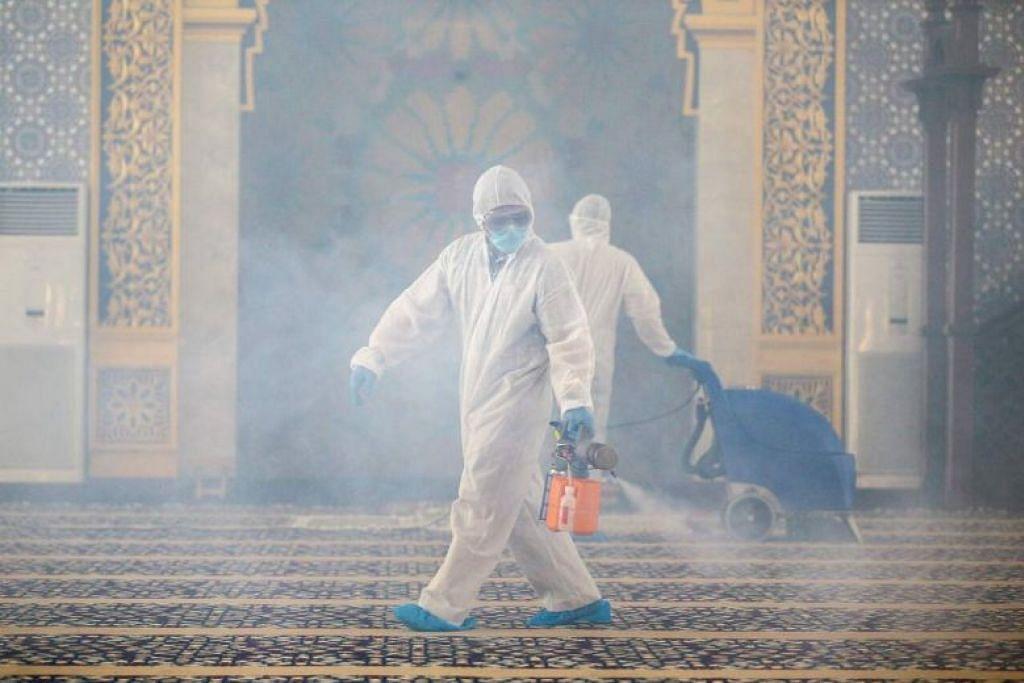Dalam satu gambar pada 17 Mac, para pekerja memakai sut perlindungan untuk menyah jangkit sebuah masjid di Brunei.
