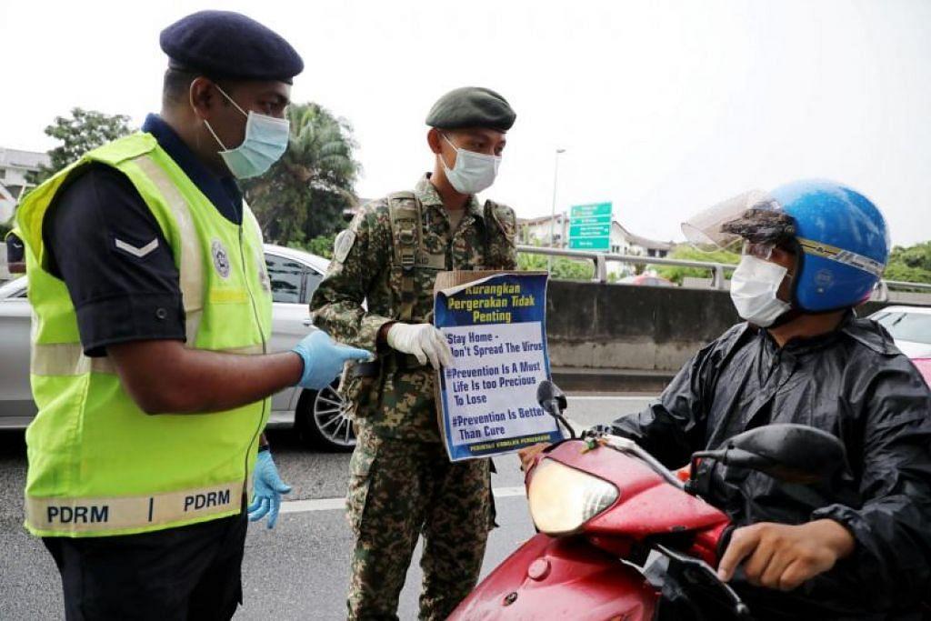 Seorang tentera dan pegawai polis yang memakai pelitup menunjukkan pelekat kepada seorang penunggang motorsikal di satu sekatan jalan raya di Kuala Lumpur pada 23 Mac.