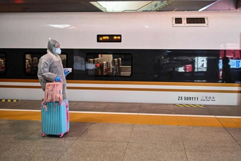 Seorang wanita memakai sut perlindungan menaiki kereta api, salah satu hentian adalah di Wuhan, di sebuah stesen di Shanghai pada 28 Mac.
