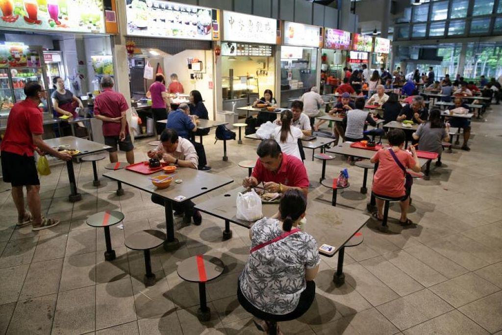 Para pelanggan duduk pada jarak yang ditandakan di Pusat Penjaja Bedok.