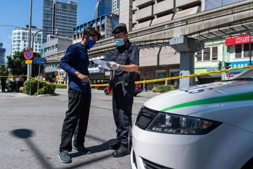 Gambar diambil pada 25 Mac, 2020,menunjukkan seorang pegawai polis memeriksa dokumen perjalanan di Kuala Lumpur.