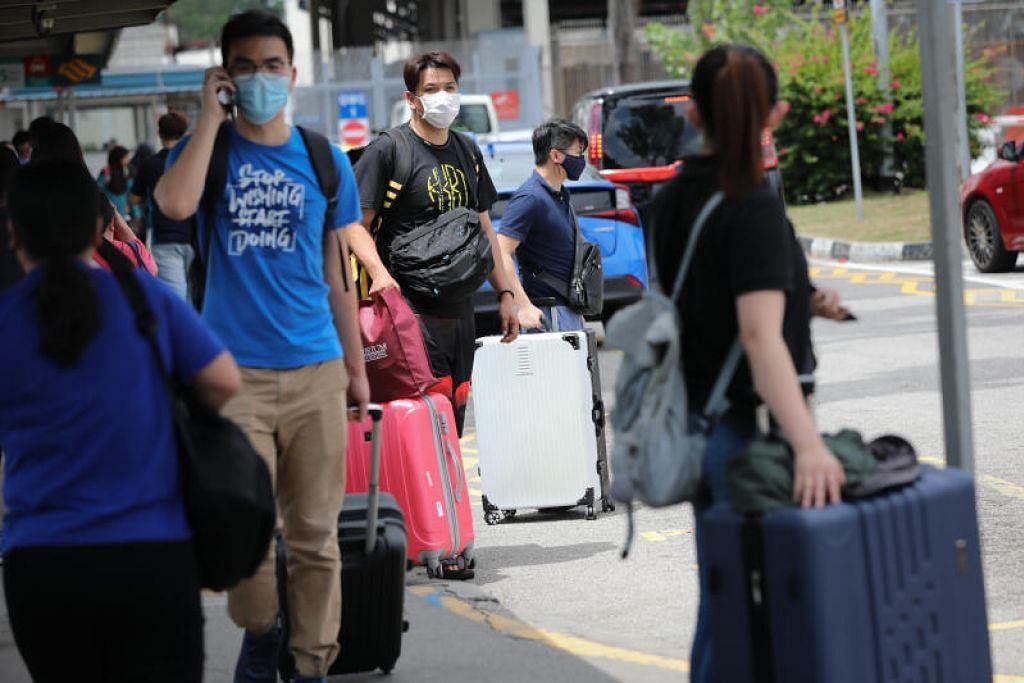 CABARAN PEKERJA: Warga Malaysia dilihat dengan beg-beg mereka di stesen kereta api di Pusat Pemeriksaan Woodlands pad 17 Mac lalu selepas Malaysia mengumumkan langkah menutup sempadan selama dua minggu bagi membendung penularan koronavirus, menyebabkan keadaan sesak di Tambak Johor.