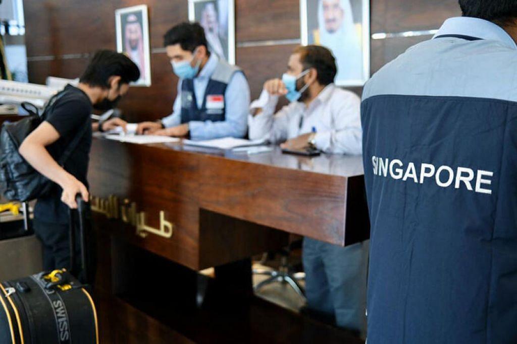 PULANG KE SINGAPURA: Seorang pelajar memberi butirannya kepada pegawai bertugas di Lapangan Terbang Antarabangsa King Abdulaziz di Jeddah, sebelum pulang ke Singapura semalam.