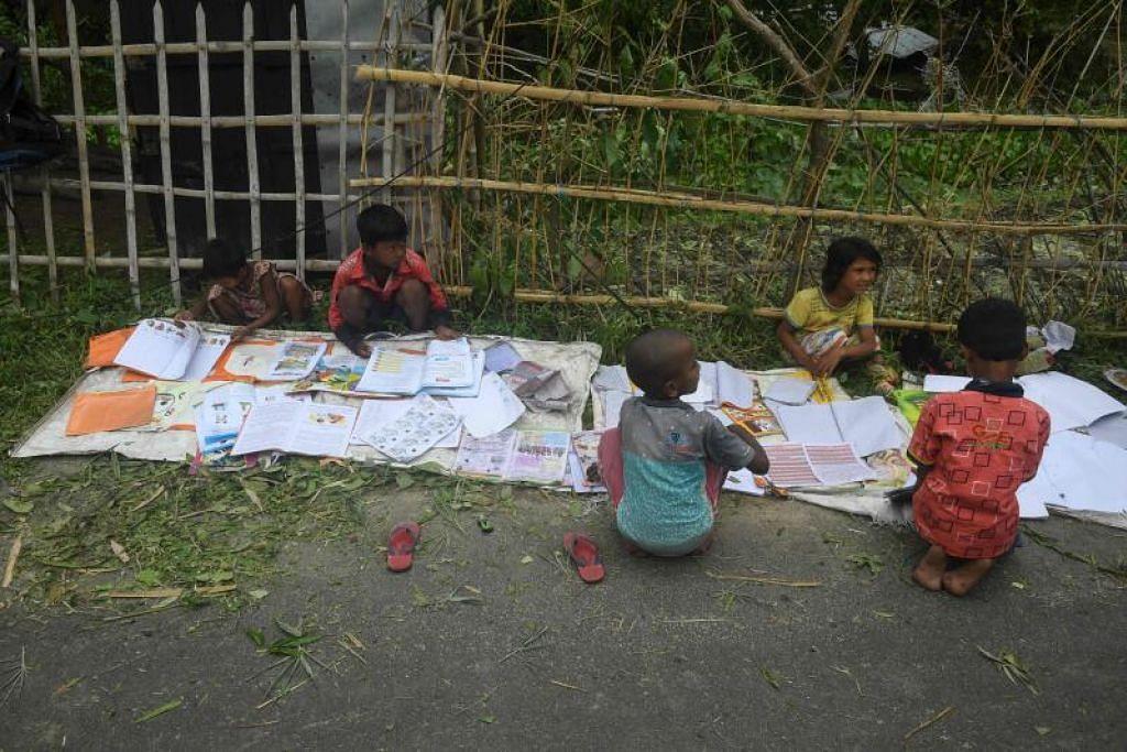 BENCANA ALAM: Kanak-kanak dilihat menjemur buku-buku sekolah mereka selepas hujan lebat akibat Taufan Amphan di kawasan Khejuri, timur Midnapore, Bengal Barat, semalam.