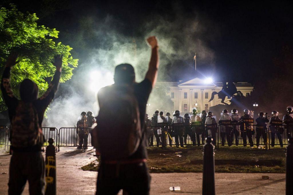 BANTAH DI LUAR RUMAH PUTIH: Penunjuk perasaan berkumpul dan berhadapan dengan pasukan polis yang mengawal di kawasan luar Rumah Putih. - Foto EPA-EFE