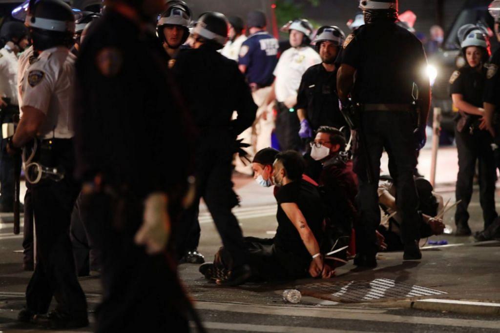 BERTUKAR GANAS: Bantahan tunjuk perasaan seringkali bertukar ganas pada sebelah malam dan beberapa orang kelihatan diberkas pihak berkuasa. - Foto AFP