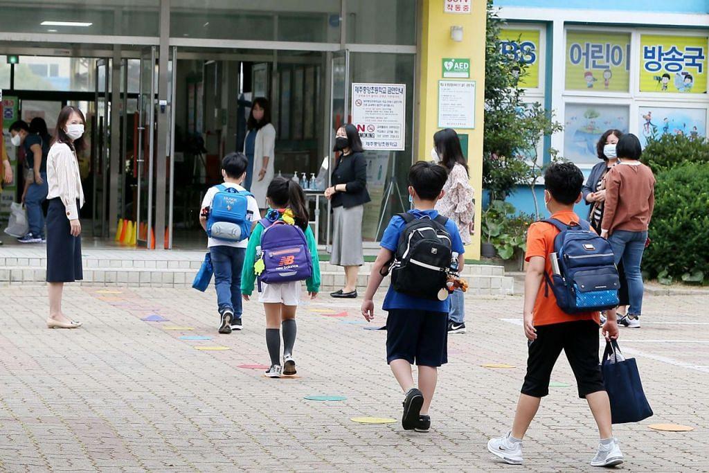 JARAK SELAMAT: Murid tiba di kawasan sekolah dan mengamalkan jarak selamat sesama mereka di sebuah sekolah rendah di Pulau Jeju, Korea Selatan. - Foto EPA-EFE