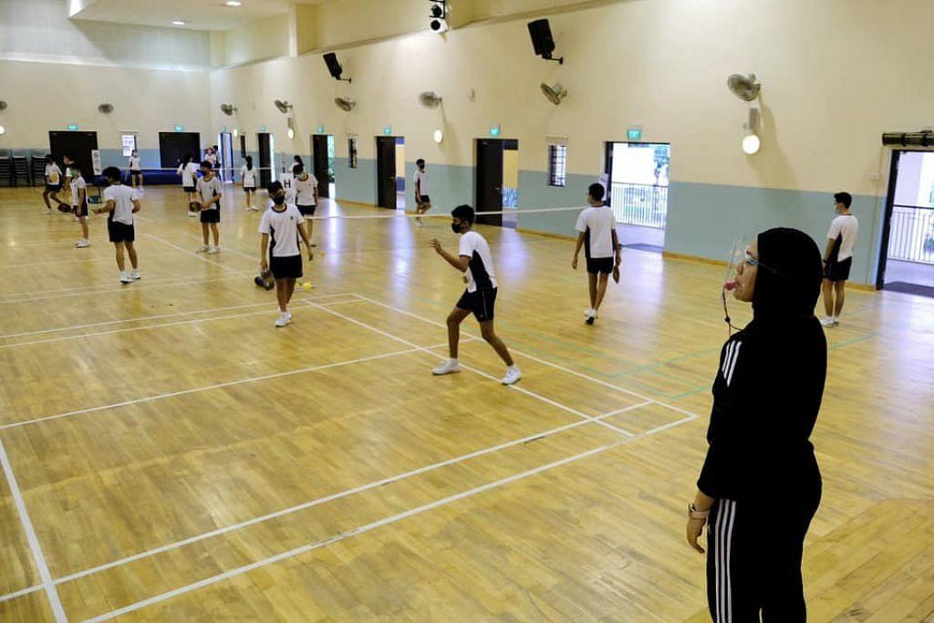 Pelajar Menengah 2 di Sekolah Menengah Ngee Ann bermain 'pickleball' sambil mematuhi langkah pengurusan selamat.