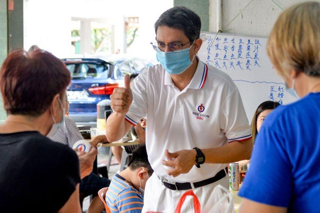 KEKALKAN SEMANGAT KAMPUNG: Dr Faishal (tengah) mendekati penduduk di sebuah kedai kopi di Blok 605 Yishun kelmarin. - Foto BH oleh HARITH MUSTAFFA