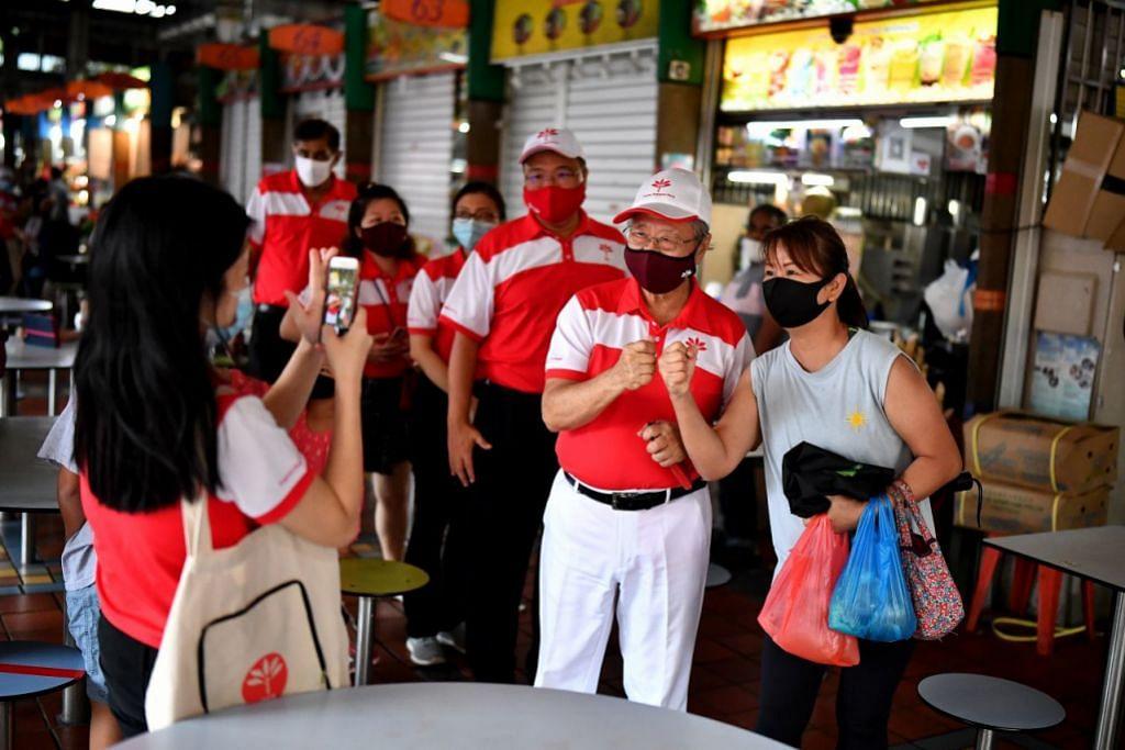 TETAP BERSEMANGAT: Walau tumpas, Dr Tan Cheng Bock (dua dari kanan) yang menerajui Parti Kemajuan Singapura (PSP) di GRC West Coast mengucapkan terima kasih dan bergambar dengan penduduk di Pusat Makan Ayer Rajah semalam. - Foto BH oleh LIM YAOHUI