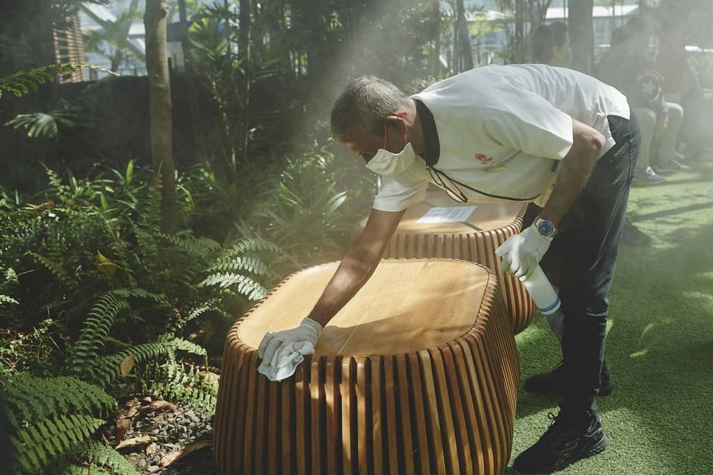 PASTIKAN BERSIH: Seorang pekerja pembersihan disinfektasi tempat duduk di Foggy Bowls di Canopy Park. -Foto TED CHEN, JEWEL CHANGI AIRPORT