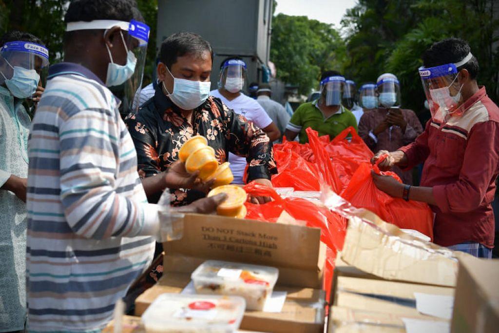 TERIMA MAKANAN RAYA: Para pekerja asing yang tinggal di asrama diberi makanan briyani dan pencuci mulut sempena Hari Raya Haji.