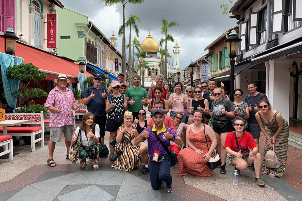 PENDAPATAN MEROSOT: Sejak pandemik Covid-19 melanda, pemandu pelancong bebas. Encik Basirun Mansor (paling depan, berbaju ungu) kehilangan 90 peratus pendapatannya kerana ketiadaan pelancong yang datang mengunjungi Singapura. Gambar beliau bersama sekumpulan pelancong di kawasan Kampung Glam ini diambil sebelum berlakunya pandemik Covid-19. – Foto MONSTER DAY TOURS