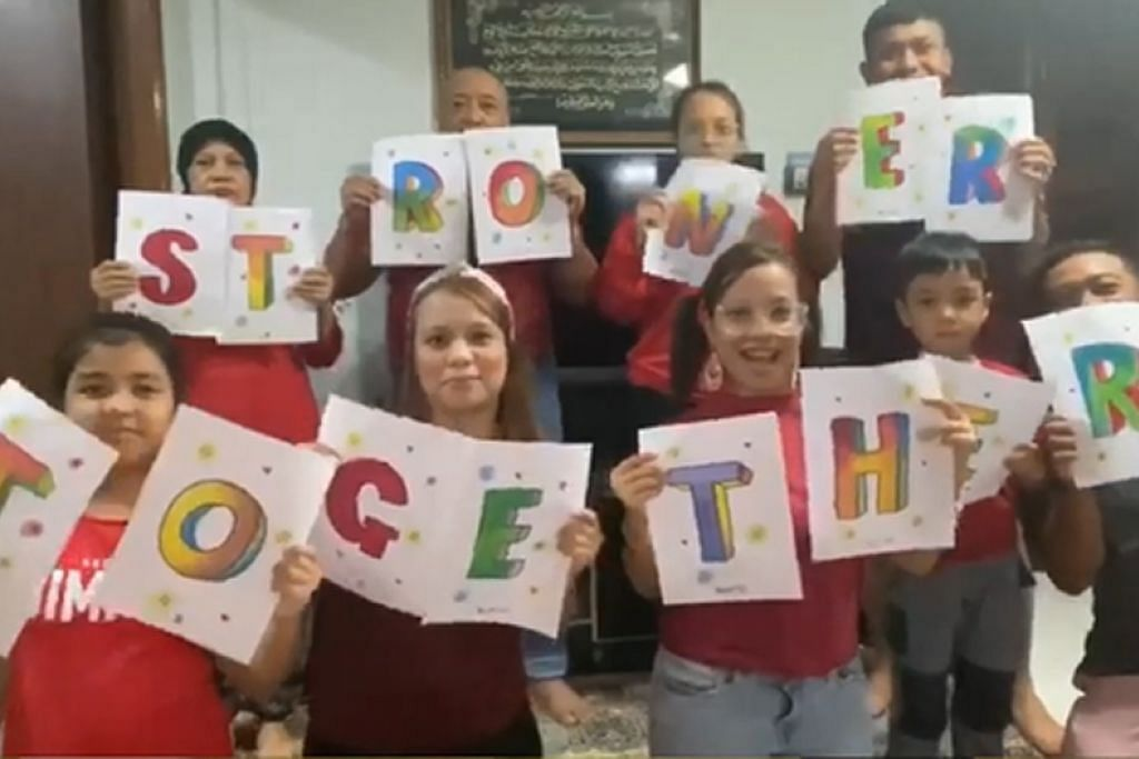 SAMBUTAN BERSAMA KELUARGA: Tahun ini, Cik Norrizah Noordin (barisan atas, kiri) telah melibatkan keluarganya untuk menyertai video Persatuan Rakyat (PA), PAssionArts, untuk Hari Kebangsaan ini. - Foto ihsan NORRIZAH NOORDIN
