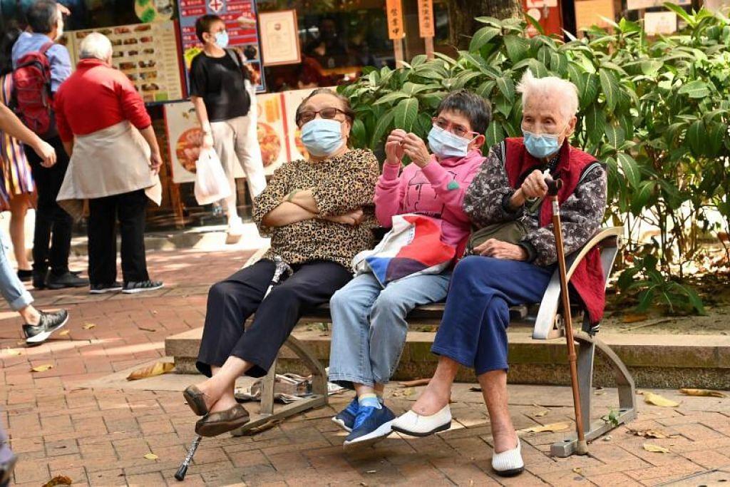 KEADAAN SEMAKIN MERUNCING: Beberapa penduduk Hong Kong menanti di luar pusat ujian jangkitan Covid-19 sedang jumlah kes di negara ini kian meningkat membawa pada kembara gelembung udara antara Hong Kong dan Singapura terpaksa ditunda sehari sebelum pelancaran semalam (Ahad, 21 November). - Foto PETER PARKS/AFP