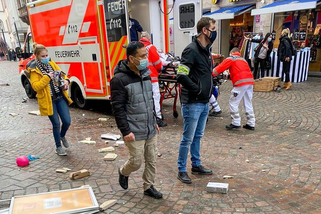 Polis dilihat sedang mengawasi kawasan sedang pekerja penyelamat menolak seorang yang telah tercedera dalam sebuah ambulans di kawasan kejadian selepas sebuah kereta melanggar pejalan kaki di bandar Trier, barat Jerman pada 1 Disember 2020. -