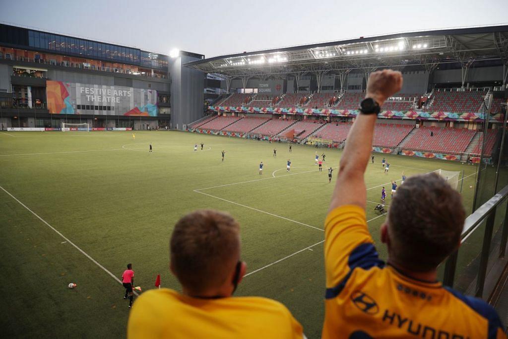 Peminat dilihat sedang menonton perlawanan antara Tampines Rovers dengan Hougang United dari luar stadium Our Tampines Hub pada 17 Oktober 2020. -