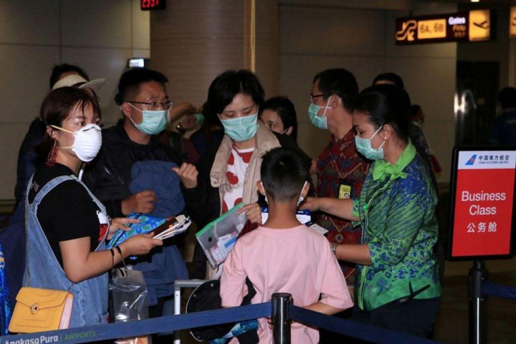 Staf lapangan terbang antarabangsa Gusti Ngurah Rai memeriksa tiket penumpang pesawat ke Guangzhou pada 4 Februari.