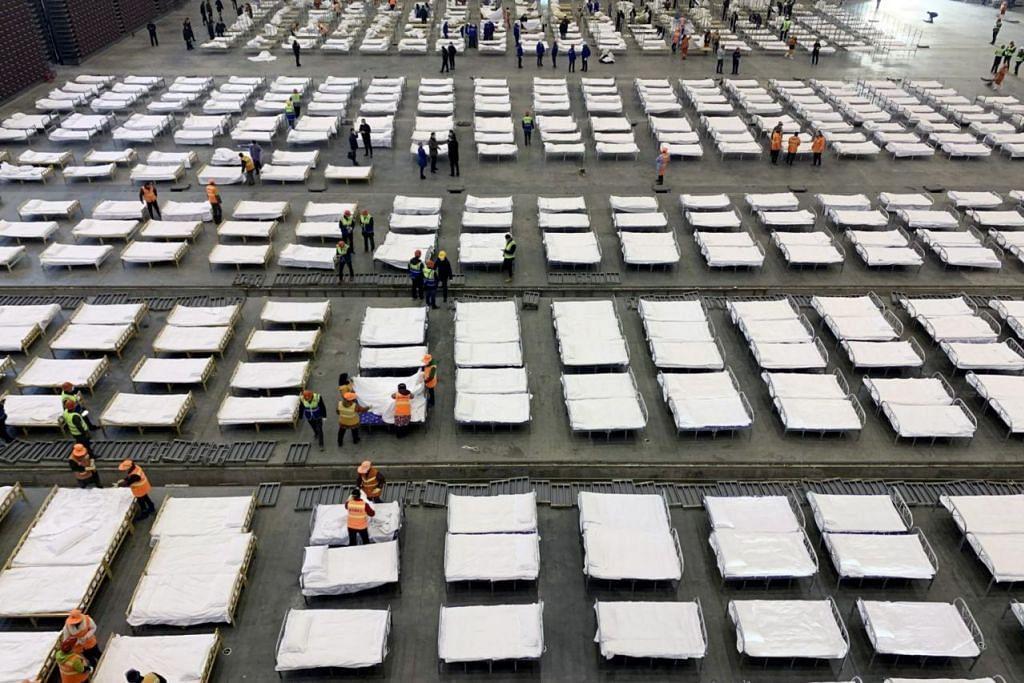 KATIL TAMBAHAN: Pekerja menyusun katil di hospital mudah alih dengan 2,000 katil yang dibangunkan di sebuah pusat pameran di Wuhan.