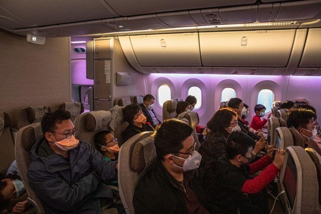 Para penumpang mengenakan pelitup muka di dalam pesawat. FOTO: EPA-FREE