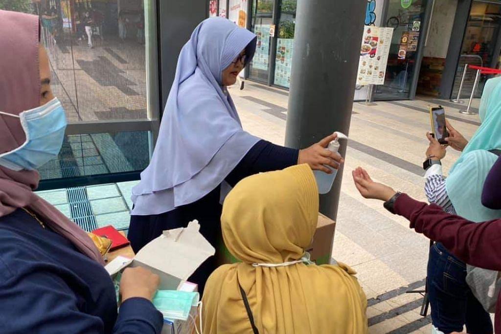 GOTONG-ROYONG: Beberapa warga Indonesia bergotong-royong membahagi-bahagikan pelitup dan snek kepada orang ramai di kawasan Payar Lebar pada Ahad (9 Februari).