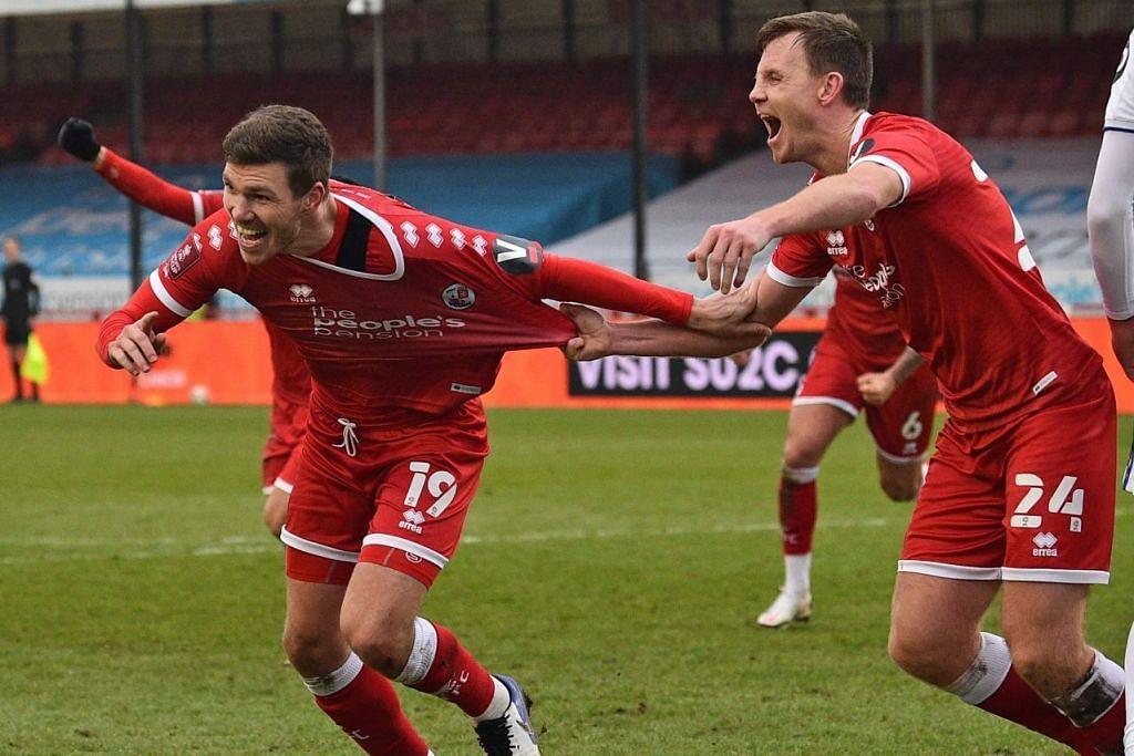 SAMBUT JARINGAN: Pemain pertahanan Crawley, Jordan Tunnicliffe (tengah) meraikan jaringannya ketika membantu kelab tahap keempat mencatat kemenangan bersejarah 3-0 ke atas Leeds. - Foto AFP