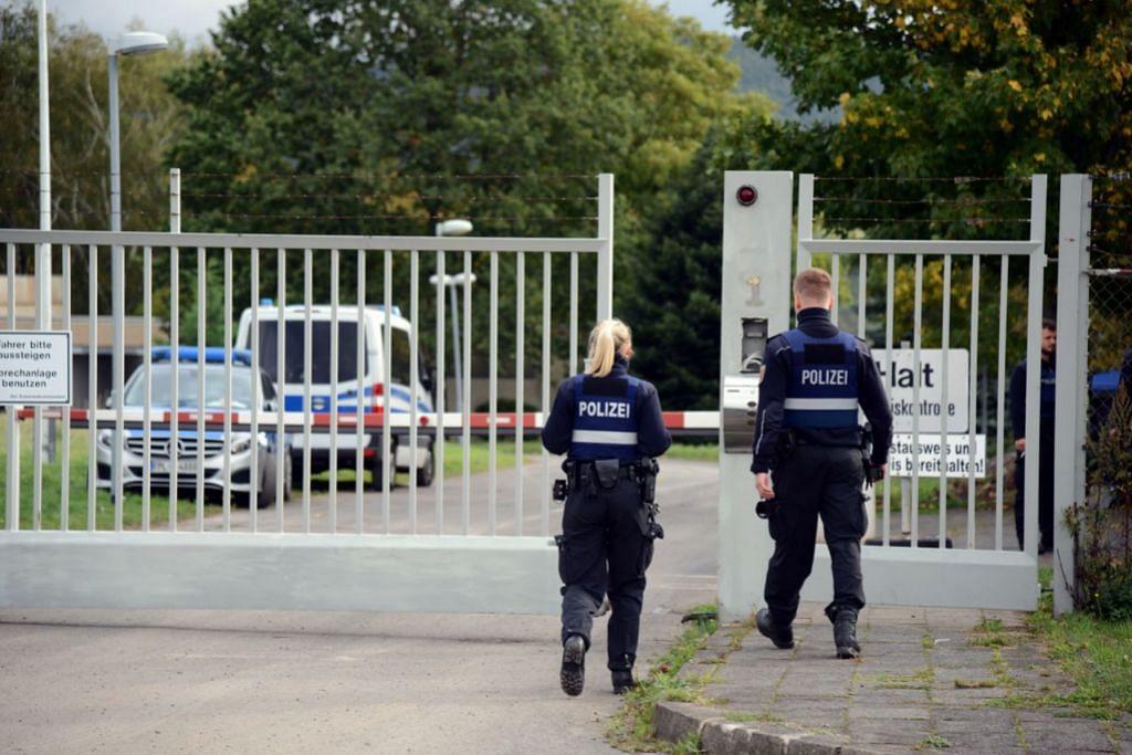 PINTU MASUK: Anggota polis memasuki kawasan perlindungan Nato (tidak kelihatan) di mana bilik operasi pasar gelap itu ditemui. - Foto EPA-EFE