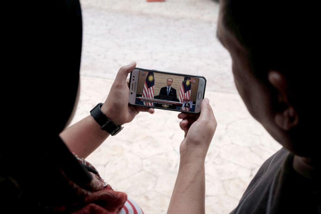 BERITA HANGAT: Orang ramai di Putrajaya menyaksikan siaran langsung ketika Perdana Menteri Malaysia, Tan Sri Muhyiddin Yassin menyampaikan perutusan khas darurat menerusi televisyen setempat melalui telefon pintar. - Foto BH oleh KHIRUL BAHRI BASARUDDIN