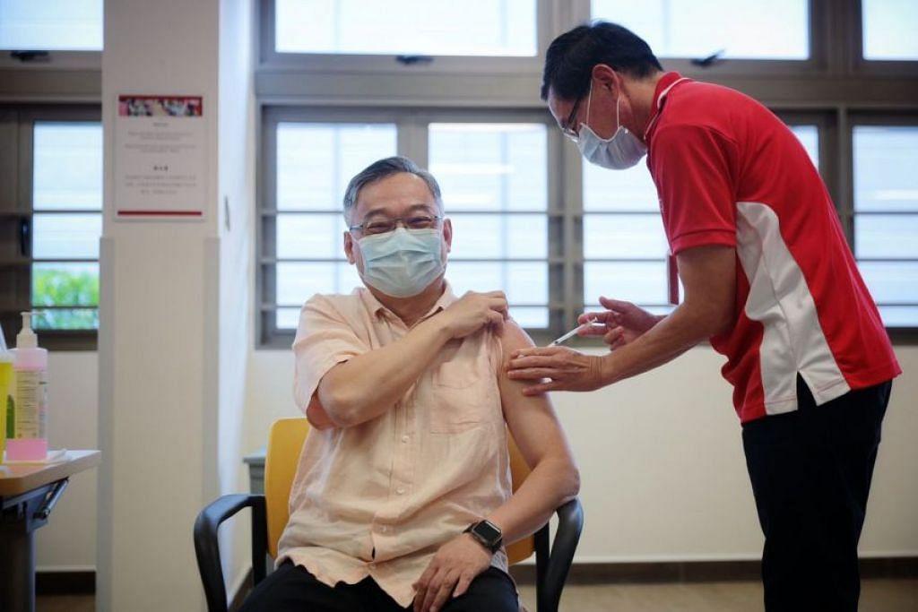 TERIMA SUNTIKAN: Menteri Kesihatan, Encik Gan Kim Yong, menerima suntikan vaksin Covid-19 daripada Dr Richard Tan di Hospital Kwong Wai Shiu pada Rabu (13 Januari). - Foto BH oleh JASON QUAH