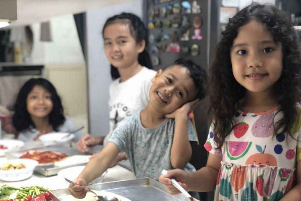Gambar Atas: Anak Cik Suhana Ab (dari kanan) Arissa, Omar dan anak saudaranya, Amaya, membuat piza di rumah pada musim hujan. - Foto ISTOCK, SUHANA AB