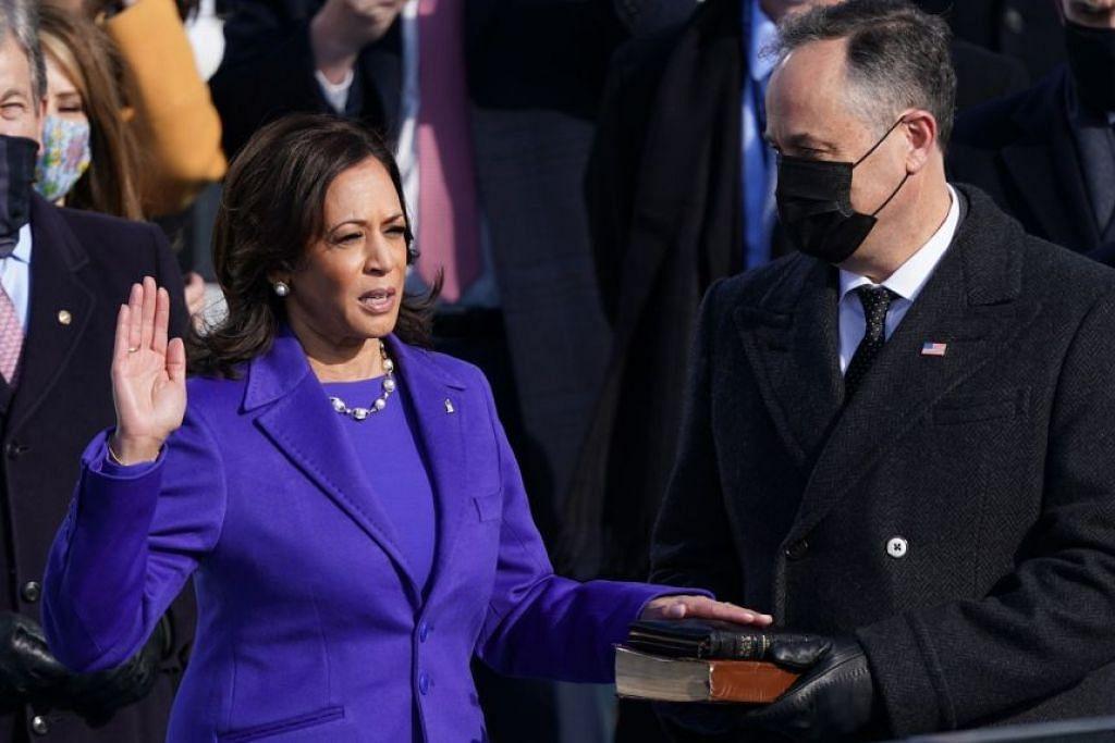 Naib Presiden AS, Cik Kamala Harris, mengangkat sumpah sambil disaksikan suaminya, Encik Doug Emhoff pada 20 Januari 2021. - Foto AFP