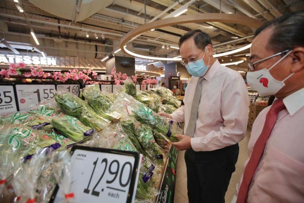 Menteri Kedua Perdagangan dan Perusahaan Encik Tan See Leng dan ketua pegawai eksekutif FairPrice Group, Encik Seah Kian Peng, (kanan) di pasar raya besar FairPrice Xtra di Parkway Parade pada Jumaat (22 Jan).