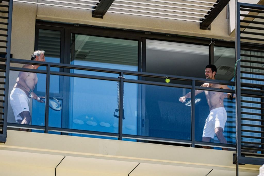 KENA KUARANTIN, BERLATIH DI BALKONI: Pemain tenis nombor satu dunia Novak Djokovic (kanan) berlatih di balkoni bilik hotel dengan seorang kakitangannya di Hotel M Suites di North Adelaide, Adelaide, Australia Selatan. - Foto AFP
