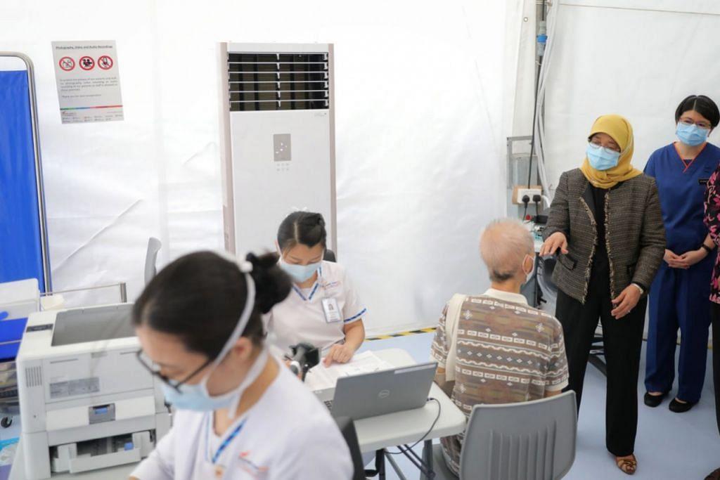MANFAAT VAKSIN: Presiden Halimah Yacob sempat meluangkan masa untuk bermesra dengan beberapa warga emas di hab vaksinasi di Poliklinik Outram. Beliau turut menerima dos pertama vaksin Covid-19 semalam. - Foto BH oleh ONG WEE JIN