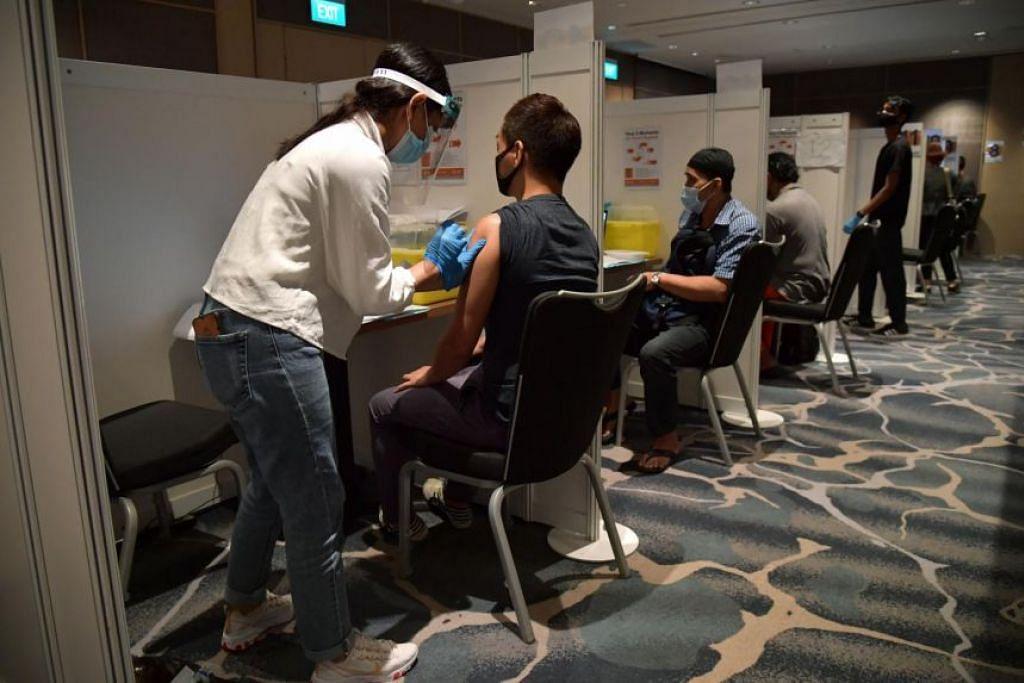 TERIMA SUNTIKAN PERTAMA: Kakitangan hotel menerima suntikan vaksin Covid-19 di Pusat Konvensyen Raffles City. - Foto BH oleh NG SOR LUAN