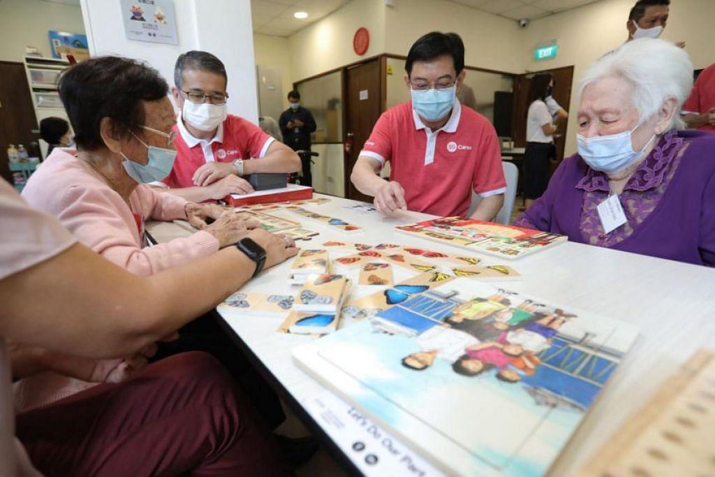INTERAKSI DENGAN GOLONGAN MEMERLUKAN: Encik Heng Swee Keat (dua dari kanan) dan Encik Edwin Tong (dua dari kiri) berinteraksi dengan peserta di pusat sukarela SG Cares Volunteer Centre di Geylang. - Foto MCI