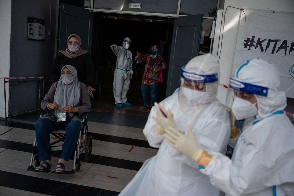 BERSIAP BUAT UJIAN: Kakitangan perubatan mengenakan pakaian khas untuk melakukan ujian di pusat ujian Covid-19 di Shah Alam, Kuala Lumpur, beberapa hari lalu. – Foto AFP