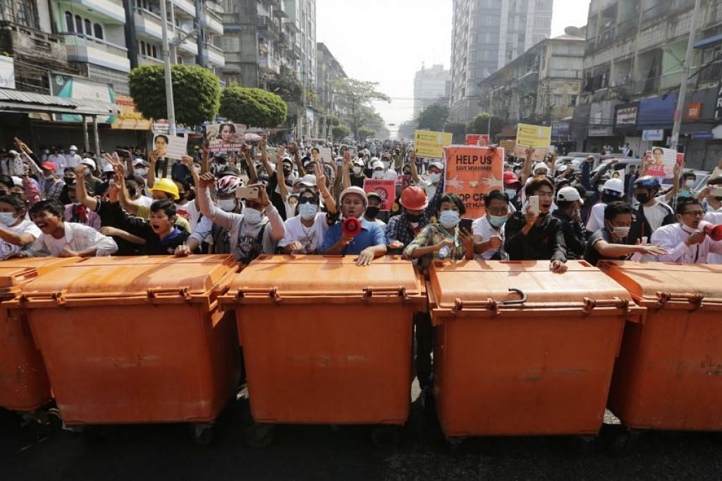 Para penunjuk perasaan berdiri di belakang penghadang sedang mereka bersemuka dengan polis rusuhan ketika bantahan di Yangon.