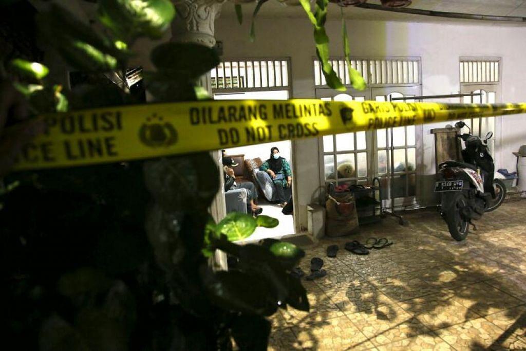 POLIS MENGEPUNG RUMAH KELUARGA PENYERANG: Inilah gambaran rumah wanita bersenjata yang ditembak mati selepas menyerang ibu pejabat polis nasional di Jakarta pada 31 Mac 2021 dengan menggunakan pistol udara piston nitrogen. - Foto DASRIL ROSZANDI/AFP