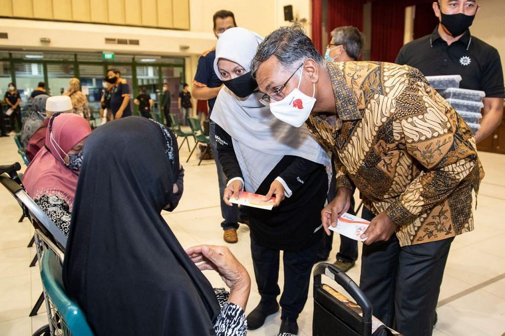 AGIH HABUAN RAMADAN: Anggota Parlimen SMC Bukit Batok, Encik Murali Pillai (kanan) dan Setiausaha Besar Persatuan Muhammadiyah, CikRoszanah Abdul Salim (sebelah Encik Murali), mengagihkan Habuan Ramadan di Hab Sukan Bukit Batok pada Ahad (11 April).