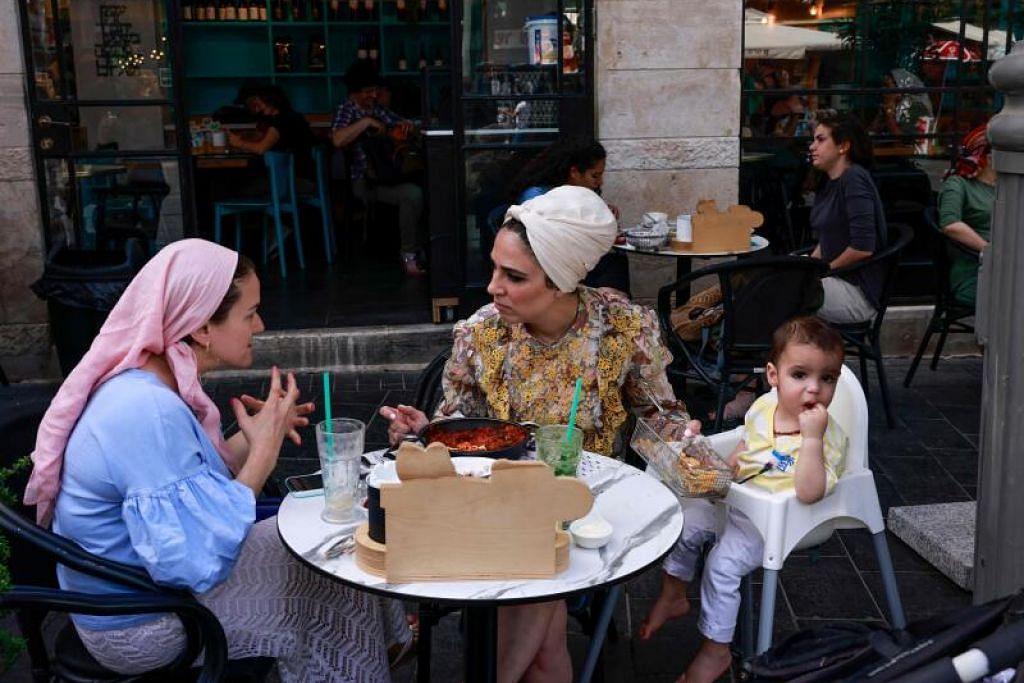 TIADA LAGI PELITUP: Wanita yang melanggani restoran di Jerusalem ini selesa berbual tanpa pelitup setelah pemerintah negara itu mengumumkan penduduk tidak lagi perlu menggunakan pelitup di tempat awam hasil jumlah kes jangkitan Covid-19 yang terkawal. - Foto AFP