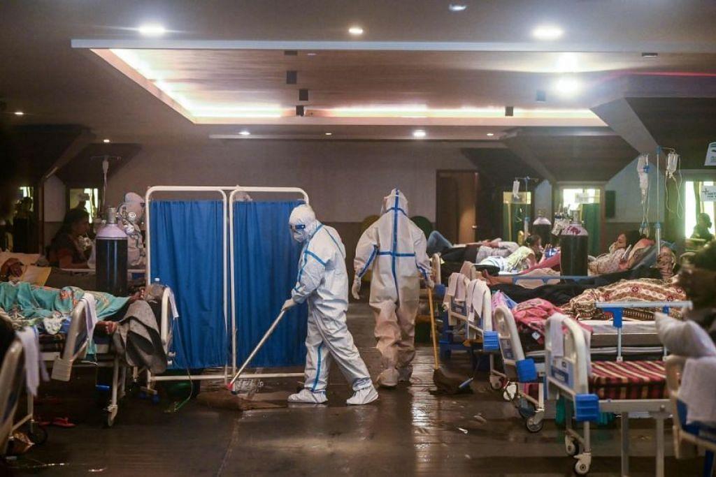Seorang pekerja kesihatan membersihkan lantai di sebuah wad sementara Covid-19 di New Delhi pada 1 Mei 2021.