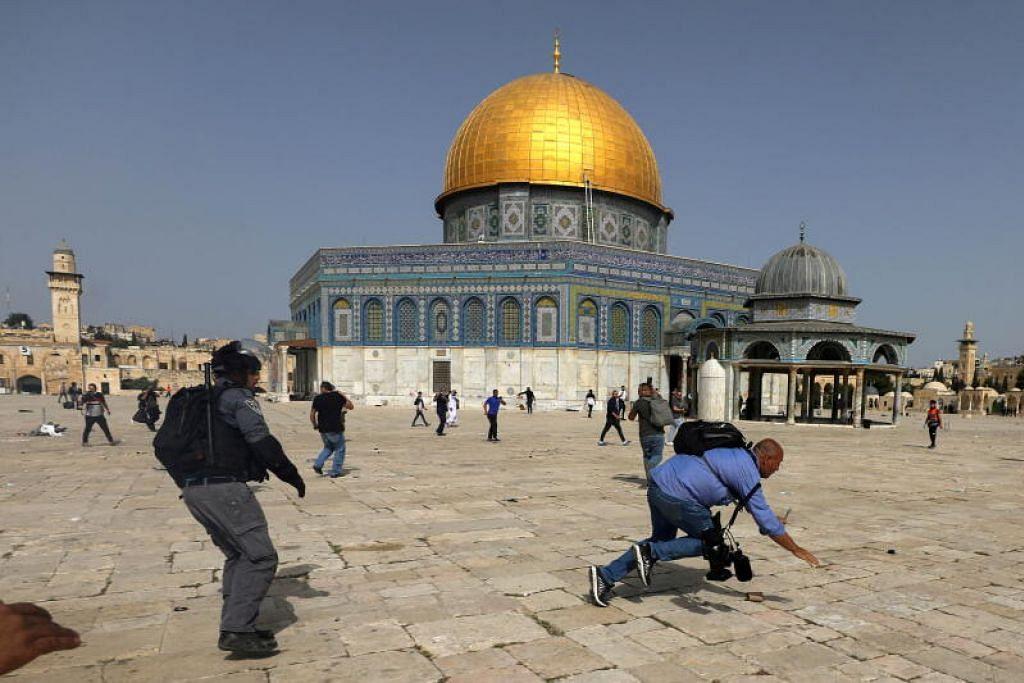 Seorang jurugambar jatuh ketika dikejar polis Israel semasa pertempuran pihak berkuasa Yahudi ke atas jemaah Islam di Masjid Al-Aqsa, Baitulmakdis. - Foto REUTERS