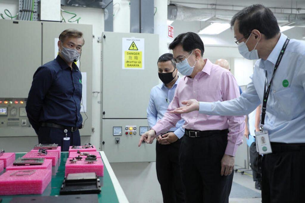 MANFAAT PELUANG:DPM Heng (dua dari kanan) bersama pengerusi bersama EST Encik Desmond Lee dalam lawatan ke sebuah syarikat tempatan baru-baru ini.