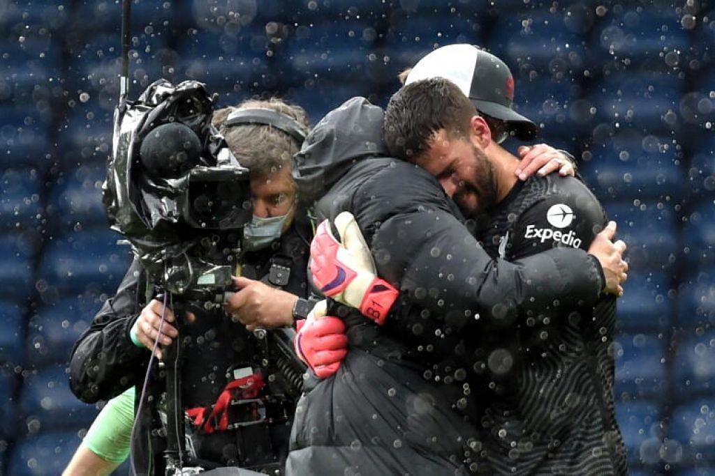 Pengurus Liverpool, Juergen Klopp (kiri) memeluk penjaga gol, Alisson selepas perlawanan Liga Perdana menentang West Bromwich Albion. – Foto EPA