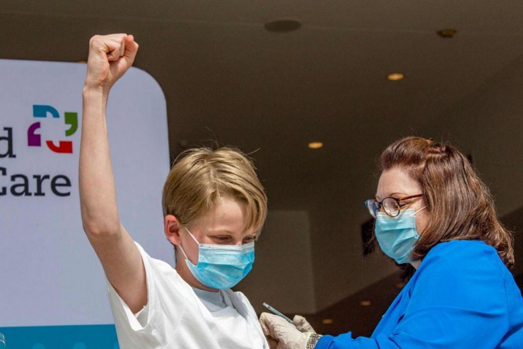 PENGALAMAN DI AMERIKA: Pelajar, Charles Muro,13 tahun (Atas), antara yang telah diberikan vaksin Pfizer di Pusat Konvensyen Connecticut, Amerika, dalam usaha negara itu membendung penularan Covid-19. - Foto AFP